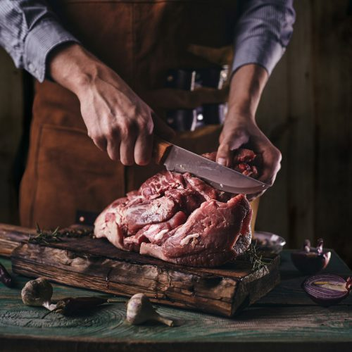 A butcher in a leather apron cuts a large piece of meat on a wooden board.